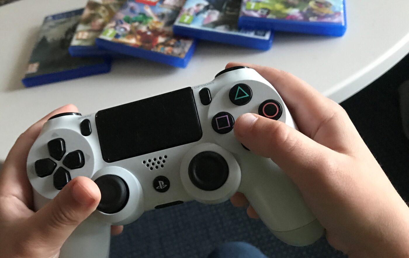 Närbild på barnhänder som håller i en PS4-kontroll. I bakgrunden ligger några olika tv-spel.