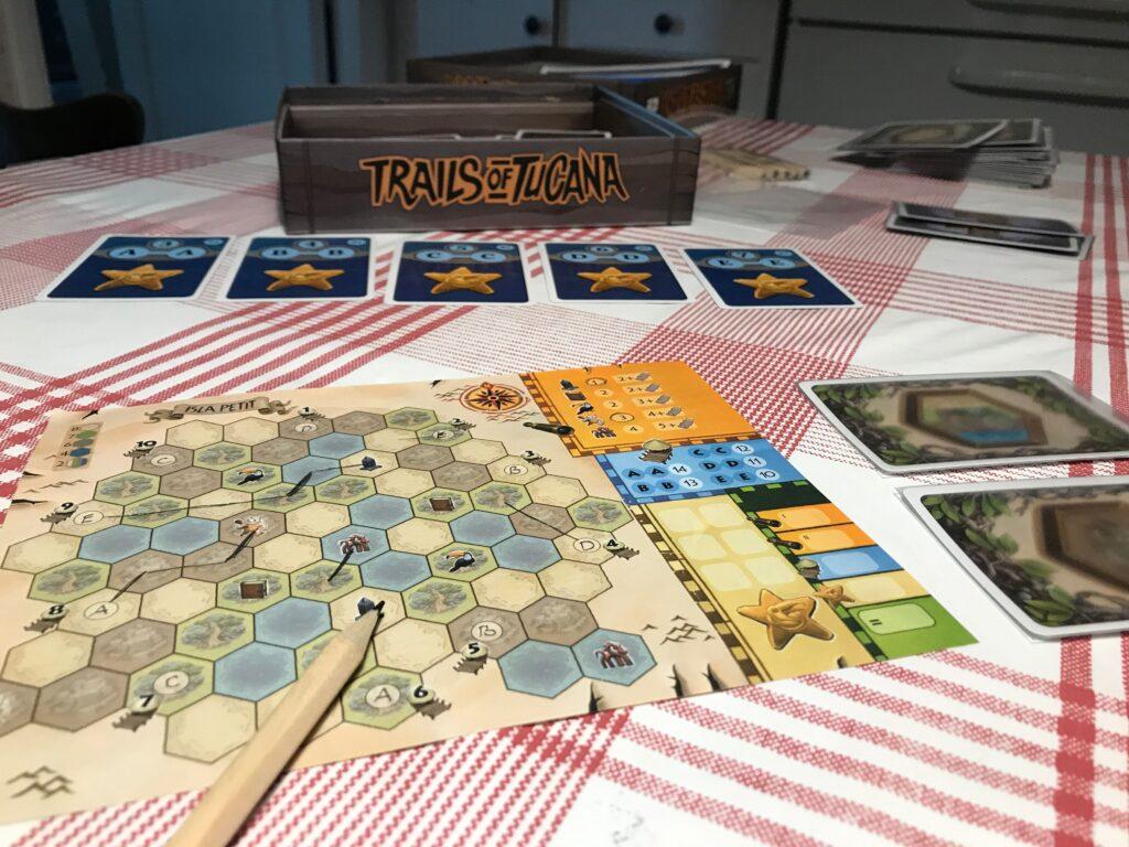 Detaljbild från Trails of Tucana. Blyertspenna och karta i förgrunden, bonuskort och spelkartong i bakgrunden.